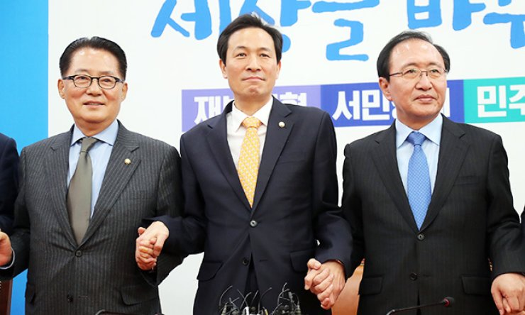 Main opposition Democratic Party of Korea floor leader Rep. Woo Sang-ho, center, joins hands with Rep. Park Jie-won, left, of the People's Party and Roh Hoe-chan of the Justice Party, ahead of their meeting at the National Assembly, Friday. / Yonhap