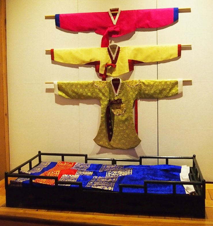 Inside the wedding ceremonial robe, women used to wear total three jackets. The innermost is the pink jacket, on top of it goes the yellow Sam-Hui-Jang jacket and finally, the most outer jacket is the green full ceremonial jacket. / Courtesy of Korea Furniture Museum