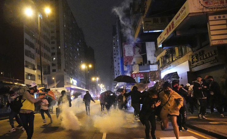 Protesters react as police fire tear gas during a demonstration in Hong Kong, early Wednesday, Jan. 1, 2020.  Chinese President Xi Jinping in a New Year's address Tuesday has called for Hong Kong to return to stability following months of pro-democracy protests that began in June over a proposed extradition law, and have spread to include other grievances and demands for more democracy. AP