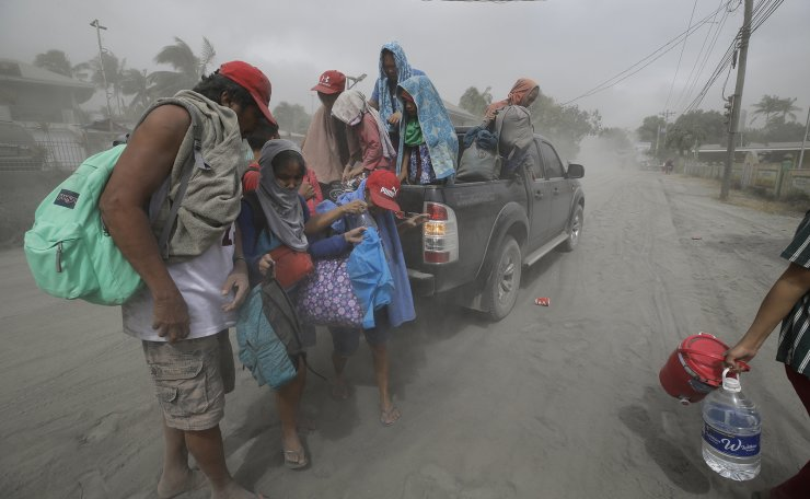 A family evacuates to safer grounds as Taal volcano in Tagaytay, Cavite province, southern Philippines on Monday, Jan. 13, 2020. AP