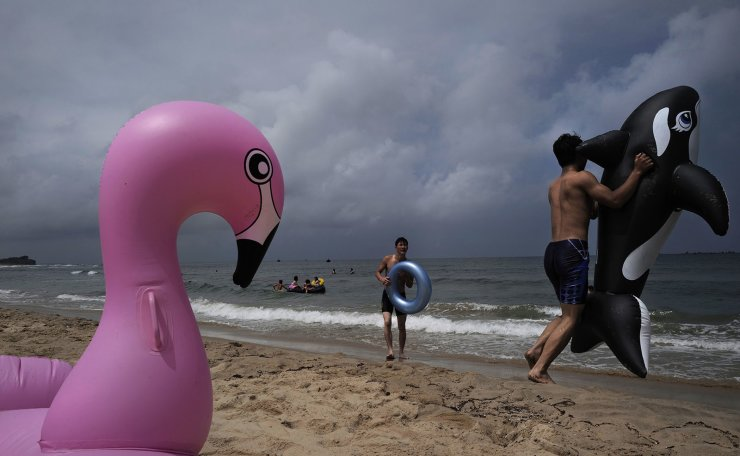 In this Sunday, July 14, 2019, photo, a man plays with an inflatable orca at Sijung Ho beach in North Korea. The beach is a popular tourist destination for locals and foreigners alike. AP