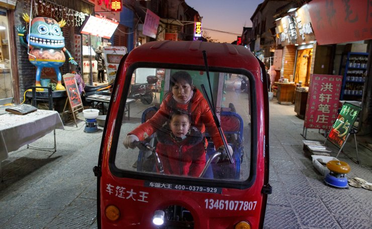 A woman and a child ride an electric tricycle in the old town of Luoyang, Henan province, China January 21, 2019. Reuters