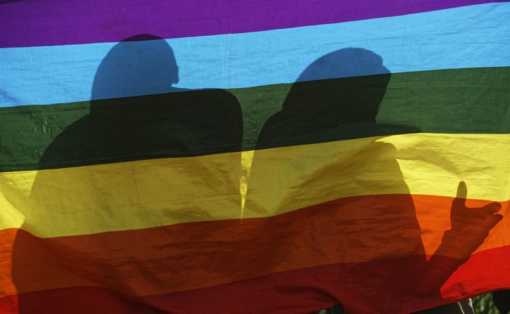 In this photo taken Friday, May 17, 2019, LGBT refugees living in Kenya stand behind a rainbow flag as they protest against their treatment by authorities, outside an office of the UN refugee agency UNHCR in Nairobi, Kenya. Kenya's High Court is due to rule Friday, May 24, 2019 on whether laws that criminalize same sex relations are unconstitutional. AP