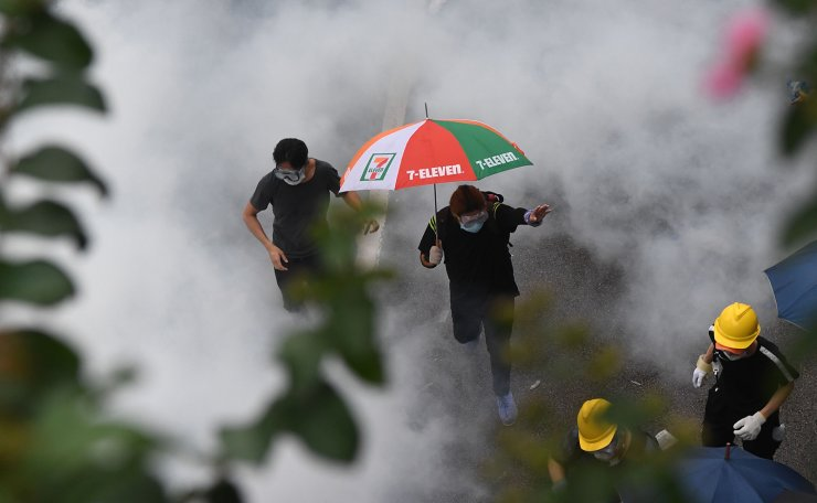 Protesters run after police fired tear gas during a rally against a controversial extradition law proposal outside the government headquarters in Hong Kong on June 12, 2019. AFP
