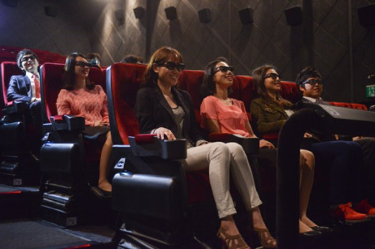 Moviegoers sit in vibrating chairs in a 4D theater, watching a movie with 3D glasses at CGV Chungdam in Sinsa-dong, southern Seoul. The theater is installed with equipment to support 4D effects, including seat vibration, jets of air or water, mist, smoke, lightning, aromatic vapors and bubbles. / Courtesy of CGV