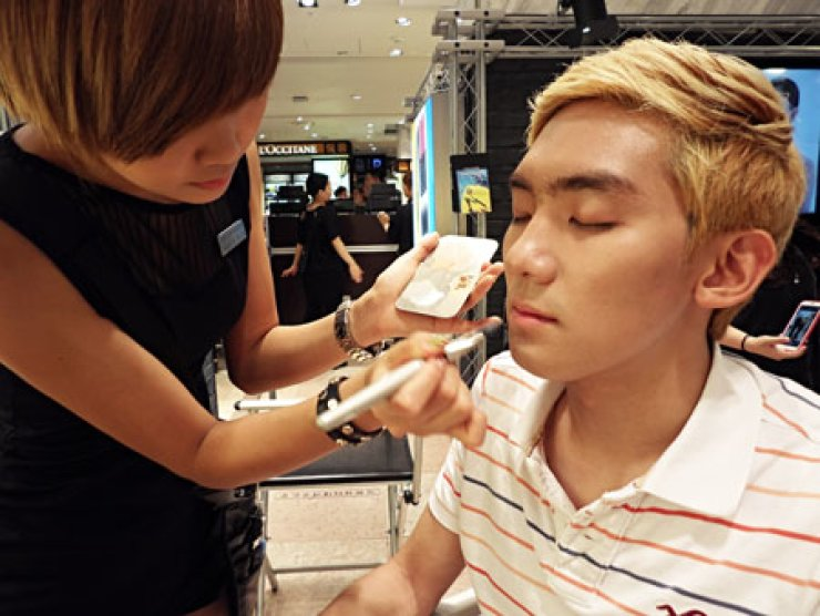 Lee Cu-bin, a 20-year-old college student, receives a makeover from makeup artist Hyun Ki-seoun at the Make Up For Ever booth in Lotte DepartmentStore in central Seoul, Tuesday. Hyun said more men visit the store to buy cosmetics to cover blemishes. / Korea Times photo by Yoon Sung-won