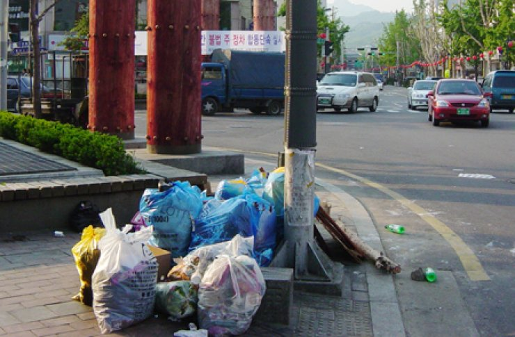Piles of garbage have appeared on a street in Jongno, downtown Seoul. A lack of trash cans leaves the streets of the city swamped with litter. <br />/ Korea Times file