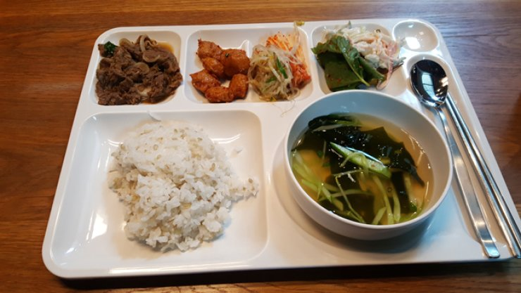 The YG cafeteria's lunch last Wednesday consisted of multi-grain rice, cold sea mustard soup, bulgogi (Korean grilled marinated beef), spicy fish ball, seasoned bean sprouts, kimchi and salad. / Korea Times photo by Kim Jae-heun