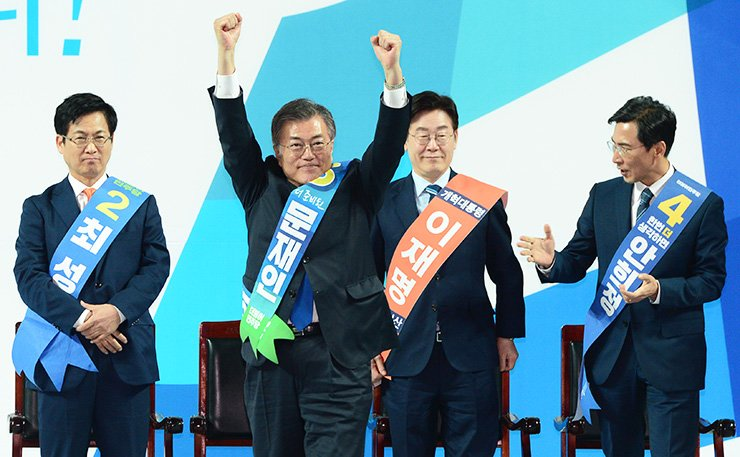 Moon Jae-in of the Democratic Party of Korea (DPK) responds to a cheering crowd at the Universiade Stadium in Kwangju Women's University in Gwangju, Monday, after winning the party's first primary in the Jeolla region for the presidential election. From left are Goyang City Mayor Choi Sung, Moon, Seongnam Mayor Lee Jae-myung and South Chungcheong Gov. An Hee-jung. / Korea Times photo by Oh Dae-geun