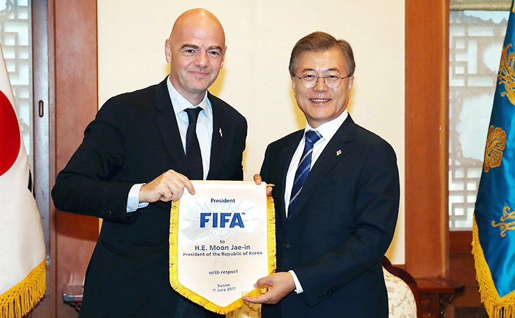 President Moon Jae-in receives a present from FIFA President Gianni Infantino, left, at Cheong Wa Dae in Seoul, Monday. / Yonhap