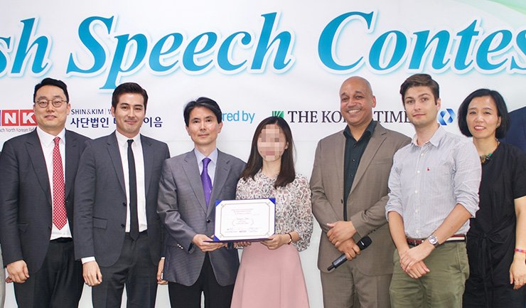 Top prize winner Young-mi, center, receives her prize certificate during the sixth English speech contest hosted by Teach North Korean Refugees (TNKR) at Shin & Kim law firm in Myeong-dong, Seoul, Saturday. The three judges are, from left, Shin & Kim lawyer Yun Jeong-min, director-actor Sean Richard Dulake, and The Korea Times Deputy Managing Editor Park Yoon-bae. TNKR co-founder Casey Lartigue Jr. is third from right and TNKR co-founder Lee Eun-koo at far right. / Courtesy of John Redmond