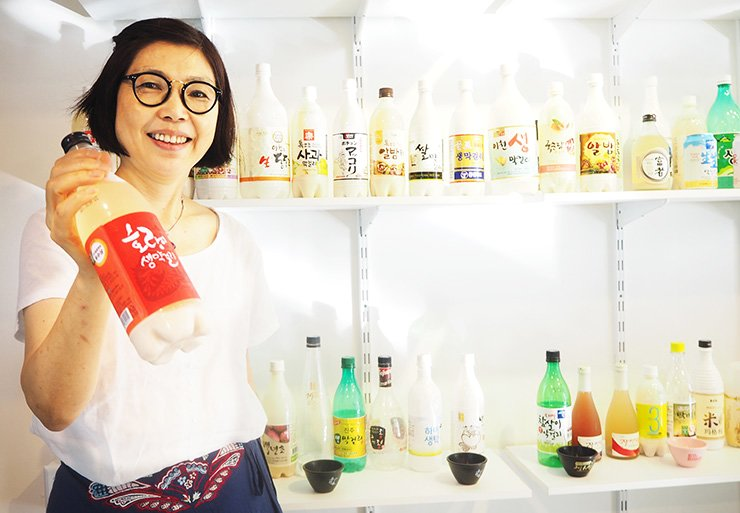 Bae Hye-jeong, president of the Korean Makgeolli Association, holds a bottle of makgeolli in front of shelves displaying different types of the traditional Korean alcoholic drink. / Courtesy of the Korean Makgeolli Association