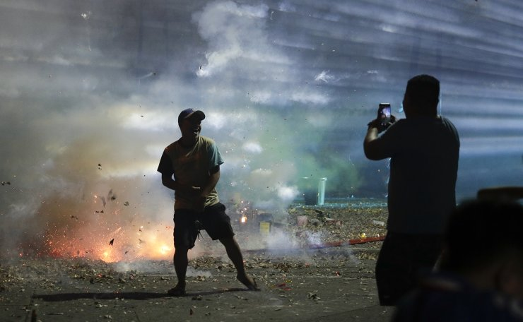 A Filipino poses for a selfie beside exploding firecrackers as they celebrate the coming of the New Year early Wednesday, Jan. 1, 2020 in Manila, Philippines. Filipinos welcome the New Year with noise and firecrackers in the belief that this will drive away bad spirits and bring in good luck. AP