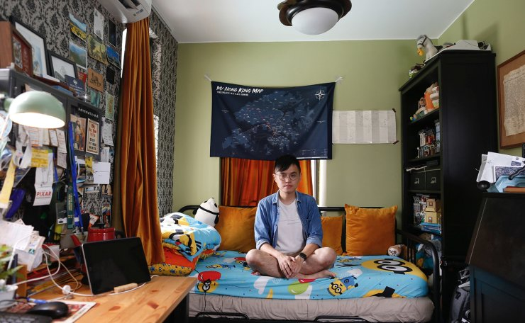 Native Hong Kong resident Michael Ho, 24, a graduate of Government and International Studies at HKBU, who lives with his parents, posing for a picture in his bedroom of his family's apartment in Hong Kong, China, June 26, 2019 and residential apartment blocks in Hong Kong, China, June 27, 2019. Ho inherited his sister's room, took down the wall separating them and now has a double room measuring 11 sq meters. He said the protests were about unjust circumstances that prevent them from living their dreams. 'It's just hopeless for young people to grow, to develop their career because of the pricing problem.' Reuters
