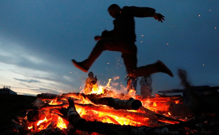 A man jumps over a campfire during the traditional Ivan Kupala Night festival at the Koza-Dereza farm near the Siberian village of Pridorozhnyy in Krasnoyarsk region, Russia, July 6, 2019. Picture taken July 6, 2019. Reuters