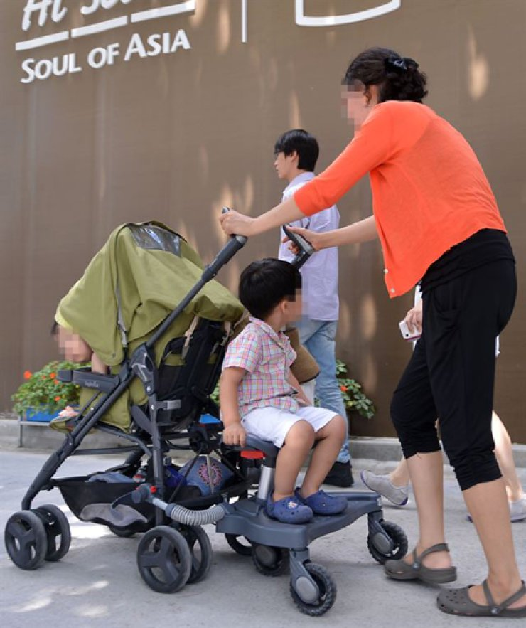 <span>A woman pushes a stroller away from a cafe after being asked to leave. More restaurants and cafes are refusing patrons with children for etiquette and safety reasons. / Korea Times file</span><br /><br />