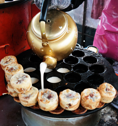 Vendors cook the deep-fried version of 'hotteok,'' or Korean pancakes, at the Namdaemun shopping district in downtown Seoul. / Korea Times photo by Yuh Suh-young