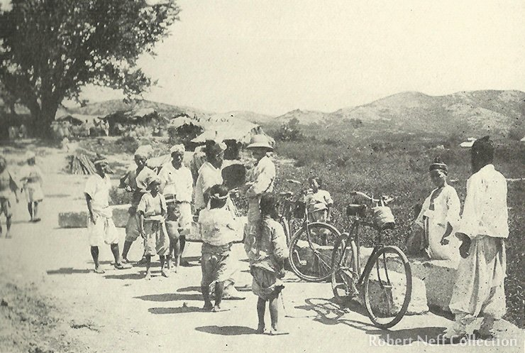 A curious crowd gathers around a Western visitor and his bicycle circa 1899.