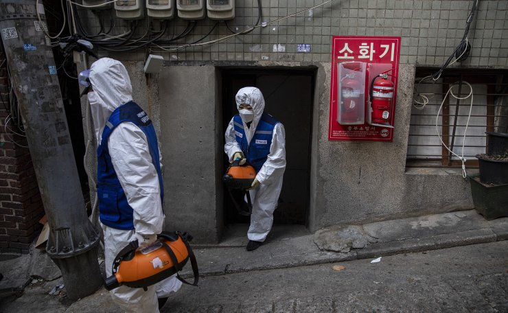 Workers wearing protective gears spray disinfectant as a precaution against the coronavirus at impoverished neighborhoods in Seoul, South Korea, Thursday, Feb. 27, 2020. Korea Times photo by Shim Hyun-chul