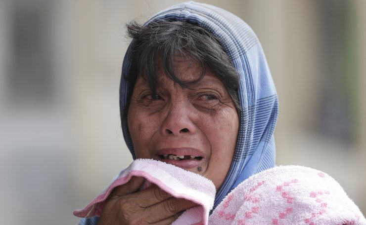Erman Batan breaks in tears over her missing husband Roberto who she has not seen since they evacuated their homes near the Taal volcano in Tagaytay, Cavite province, southern Philippines on Monday, Jan. 13, 2020. AP