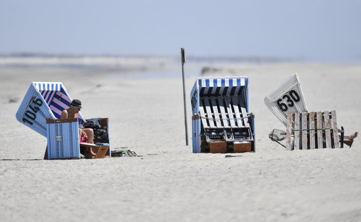 In this photo taken on Wednesday, May 15, 2019, tourists enjoy the sun in beach chairs on the car-free environmental island of Langeoog in the North Sea, Germany. AP