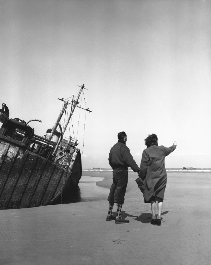 FILE - In this May 28, 1954, file photo, about ten years after D-Day, a young French couple look over the stretches of Omaha Beach in Normandy, France. At left is the wreck of an American drag-ship. AP