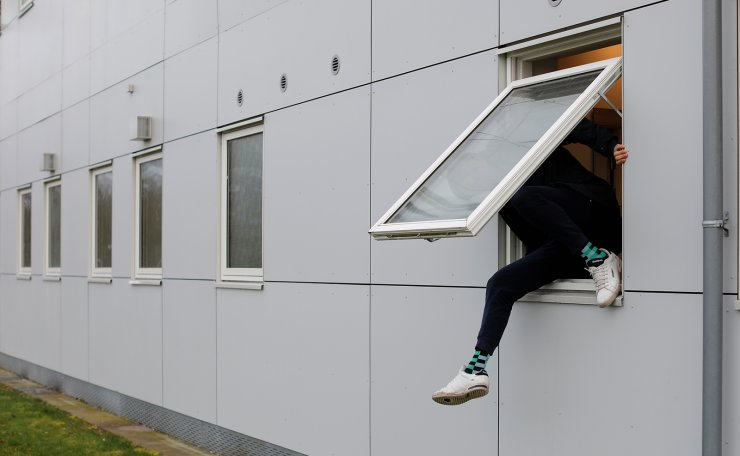 A resident climbs through a window at Kaershovedgaard, a former prison and now a departure centre for rejected asylum seekers in Jutland, Denmark, March 26, 2019. Reuters