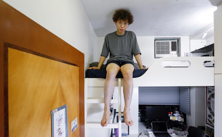 Native Hong Kong resident Fung Cheng, 25, a graphic designer, who lives in a flat with his parents and brother, poses for a picture in his five square metre bedroom of his family's apartment in Hong Kong, China June 27, 2019. Cheng vented his frustration at a system that he believes has robbed him of the chance to ever have his own home. He said Hong Kong's Beijing-backed governor Carrie Lam, who was chosen as leader in 2017 in a vote by an electoral college approved by Beijing, just didn't listen to the people. 'It's the system's problem ... they don't need a vote to be the government, there is no democracy,' he said. Reuters