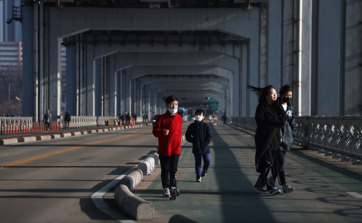 People are seen wearing face masks on the Jamsu Bridge in Seoul, South Korea, Thursday, March 19, 2020. Korea Times photo by Choi Won-suk