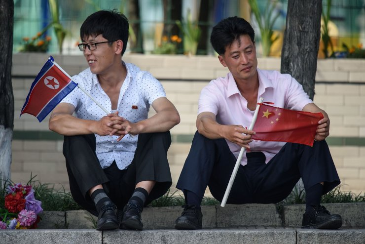 Two men sit holding North Korean and Chinese flags near Kim Il Sung square in Pyongyang on June 20, 2019, as Chinese President Xi Jinping visits the country. - Xi Jinping started a historic visit in Pyongyang on June 20, to reboot a troubled alliance, as he and North Korean leader Kim Jong Un face their own challenges with US President Donald Trump. AFP