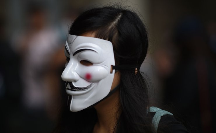 A protester, wearing a stylised Guy Fawkes mask popularised by the V For Vendetta comic book film, stands outside the High Court premises in support of activist Edward Leung, jailed for taking part in the 2016 Mongkok riots, during an appeal hearing for his period of sentence in Hong Kong on October 9, 2019. AFP