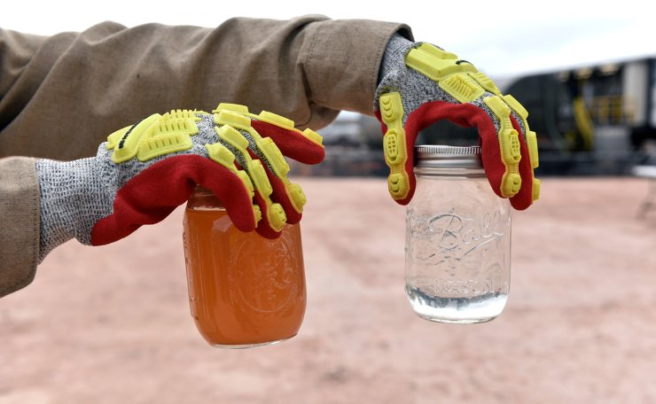 A worker holds up a jar of produced water (L) and recycled water (R) at a water recycling facility owned by Exxon near Carlsbad, New Mexico, U.S. February 11, 2019. Picture taken February 11, 2019. Reuters