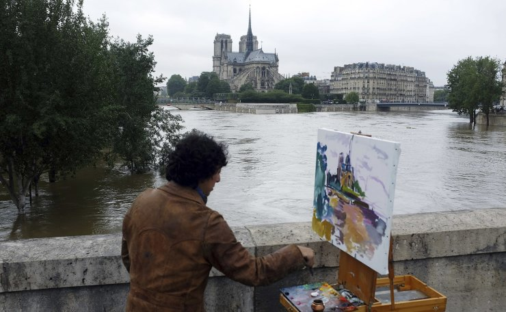 In this Friday, June 3, 2016 file photo, a man paints the Notre Dame cathedral surrounded by the flooding Seine river in Paris, France. AP