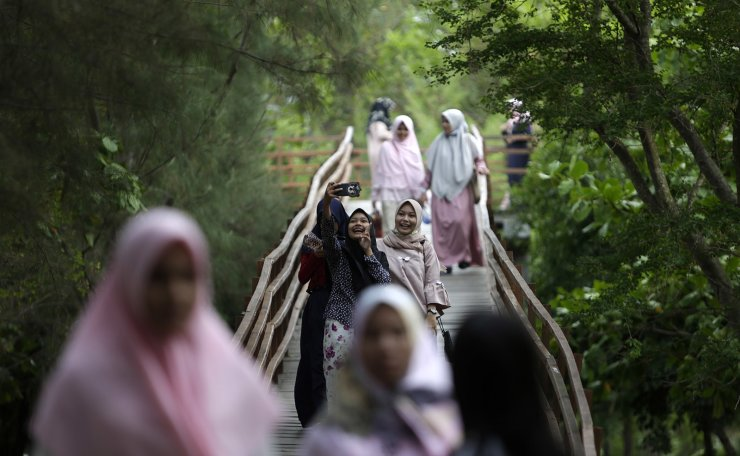 Residents walk through City Forest Park in Tibang Village, Banda Aceh, Indonesia on 23 April 2019. The City Forest, a coastal mangrove swamp, is planned as a tsunami barrier and public green area where people can relax inside city limits. EPA