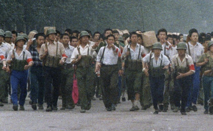 In this June 6, 1989, photo, Chinese soldiers marching away from Tiananmen point out an an Associated Press reporter taking photos, which was against the regulations of martial law that had been declared May 20 and later gave chase, firing twice before the reporter escaped near the International Hotel in Beijing. The Chinese army had fought its way into Tiananmen Square the night of June 3-4 to reclaim the square from student-led demonstrators who had been protesting for democratic reforms for three weeks. AP