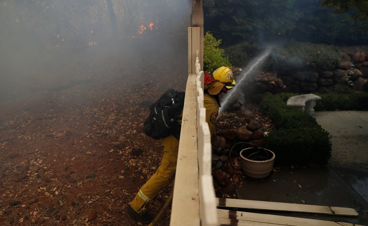 A Cal Fire firefighter work to extinguish a spot fire at a home while battling the Camp Fire in Paradise, California, U.S. November 8, 2018. Reuters
