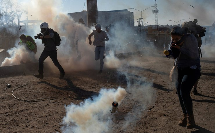 Reuters staff photographer Kim Kyung-Hoon (L) works through a cloud of tear gas which was fired by U.S. Customs and Border Protection (CBP) after migrants, part of a caravan of thousands from Central America, attempted to illegally cross the border into the United States from Tijuana, Mexico November 25, 2018. Reuters