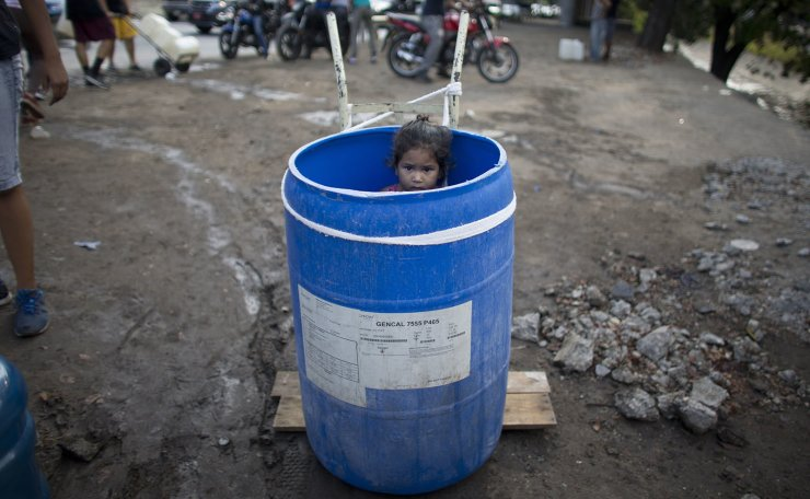 A little girl stands inside a plastic barrel while her family waits to collect water from an open pipe above the Guaire River, during rolling blackouts which affect the water pumps in people's homes, offices and stores, in Caracas, Venezuela, Monday, March 11, 2019. The blackout has intensified the toxic political climate, with opposition leader Juan Guaido blaming alleged government corruption and mismanagement and President Nicolas Maduro accusing his U.S.-backed adversary of sabotaging the national grid. AP
