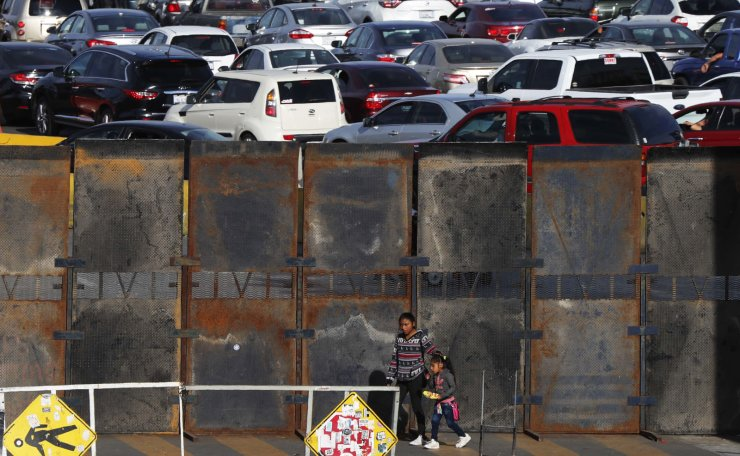 A newly erected barrier wall stands amid cars at the Mexico-U.S. border, as they wait in line to enter the U.S., as they leave Tijuana, Mexico, Monday, Nov. 19, 2018. AP