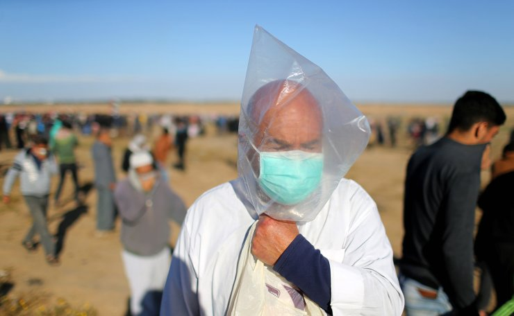 A Palestinian covers his face with a plastic bag to protect himself from tear gas fired by Israeli troops during a protest at the Israel-Gaza border fence, in the southern Gaza Strip May 3, 2019. Reuters