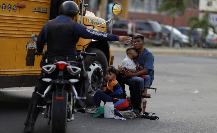 A Venezuelan police officer orders a man and his sons to move from the street where he was asking for donations, during a blackout in Maracaibo, Venezuela April 11, 2019. Reuters