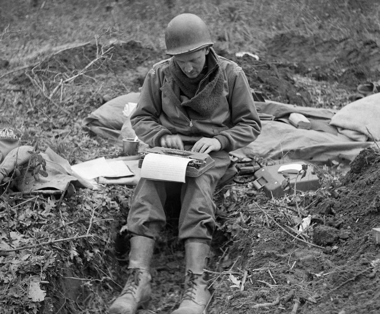 FILE - In this February 1944, file photo, Don Whitehead, Associated Press correspondent, writes his story of the landing at Anzio Beach in Italy, from a fox hole. Whitehead, known by his colleagues as