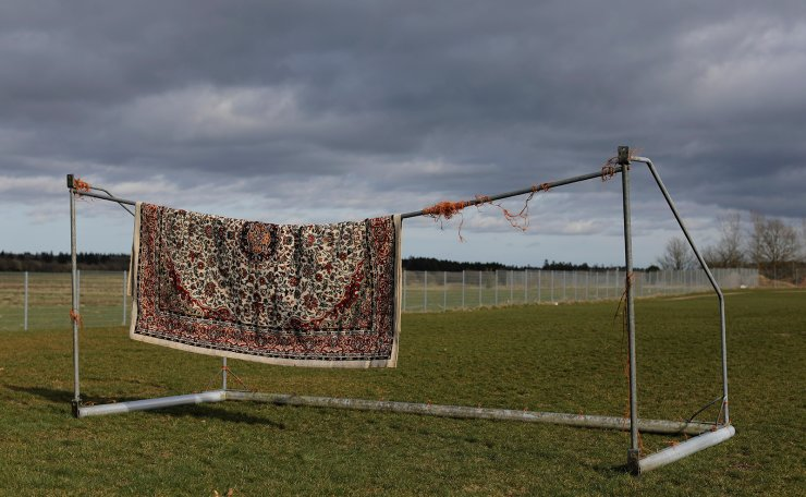 A rug belonging to a resident from Iran hangs from a football goalpost to dry after it was washed at Kaershovedgaard, a former prison and now a departure centre for rejected asylum seekers in Jutland, Denmark, March 26, 2019. Reuters