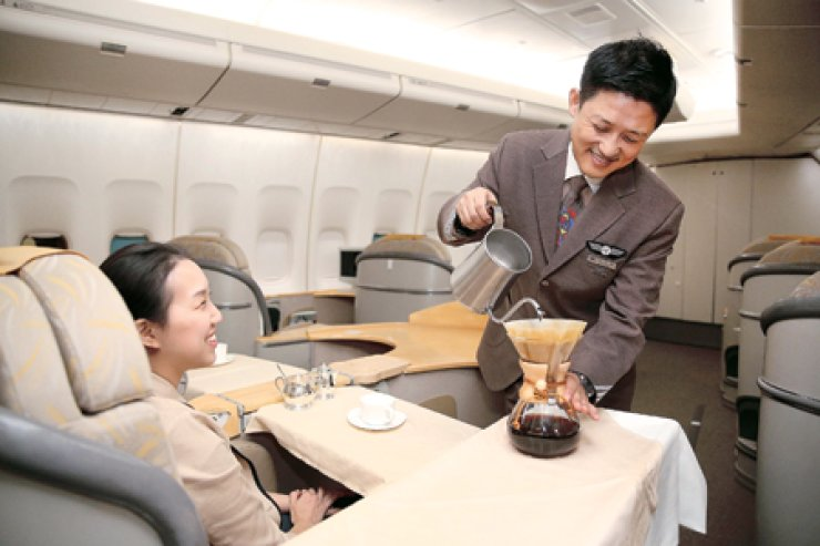Asiana Airlines senior purser Shim Jae-beom makes hand dripped coffee on a flight. Shim proposed the airline adopt the barista service, and Asiana is the only carrier offering it. / Courtesy of Asiana Airlines