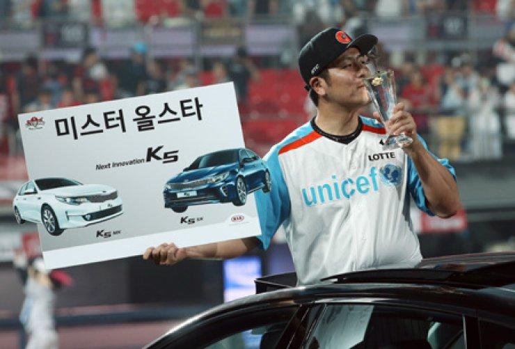 Lotte Giants catcher Kang Min-ho kisses a trophy besides a Kia Motor K5 sedan after he won the MVP prize during the Korea Baseball Organization's (KBO) All-Star game at the Suwon KT Wiz Park in Suwon, Gyeonggi Province, Saturday. / Yonhap