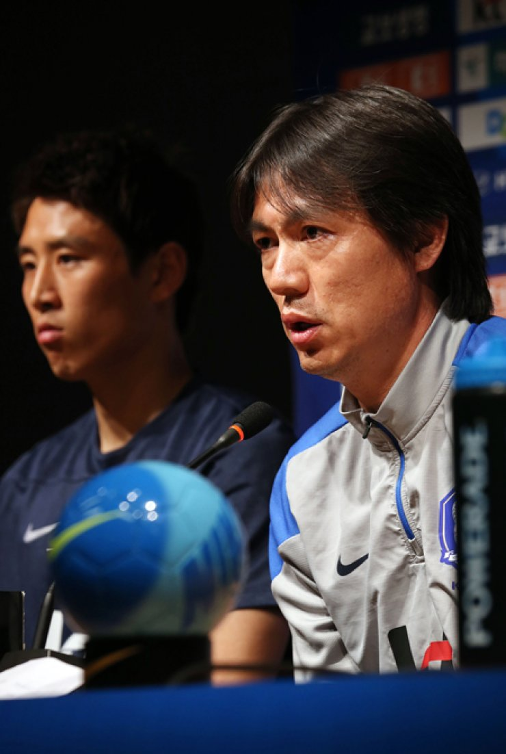 National football coach Hong Myung-bo, right, speaks during a news conference at Seoul World Cup Stadium in Mapo District, Tuesday. Hong said he will test new options in today's warm-up match against Tunisia at the stadium. At left is team captain, Koo Ja-cheol. / Yonhap
