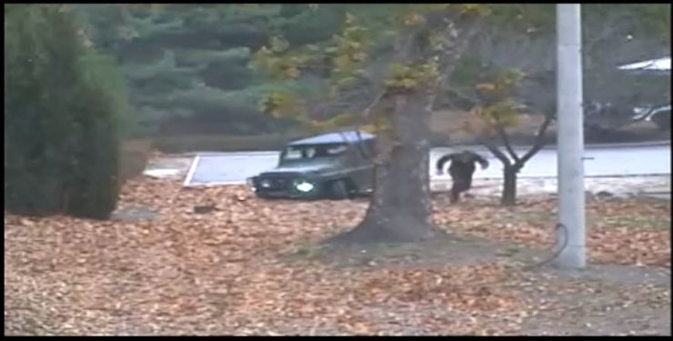 A North Korean soldier runs toward the south side of the Joint Security Area (JSA) after getting out of a vehicle stuck along a row of JSA buildings in this surveillance camera footage released by the United Nations Command, Wednesday. / Courtesy of United Nations Command