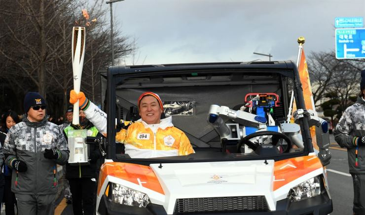 HUBO in the self-driving car with Professor Dennis Hong as a passenger during the torch relay in Daejeon on Monday. / Yonhap