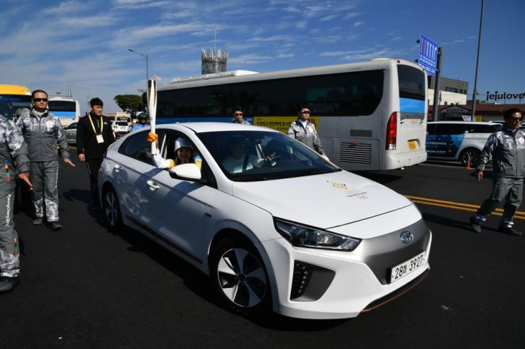 K-pop singer Kim So-hye carries the Olympic flame, riding in the Hyundai Ioniq electric vehicle, during the torch relay on Jeju Island in this Nov. 2 file photo. Kim's father drove the car. / Courtesy of Hyundai Motor