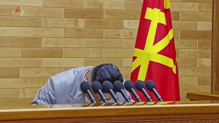 North Korean leader Kim Jong-un bows before delivering a New Year's address, broadcast by the state-run Korean Central TV, Monday. In North Korea, its leader is rarely seen bowing. Kim also wore a light grey suit instead of the dark-colored uniform he usually wears for official events. He also did not wear any badges depicting portraits of his father or grandfather. / Yonhap